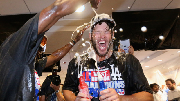 LOS ANGELES, CA - SEPTEMBER 24: Pitcher Clayton Kershaw #22 of the Los Angeles Dodgers has champagne poured on him following the Dodgers' 9-1 victory over the San Francisco Giants to win the National League West Division Championship at Dodger Stadium on September 24, 2014 in Los Angeles, California. (Photo by Jeff Gross/Getty Images)